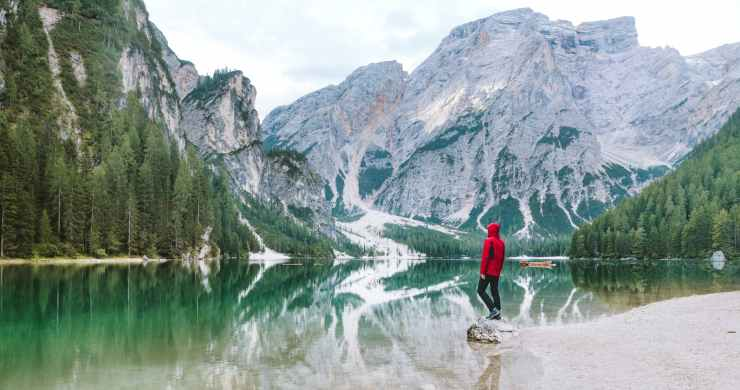 man wearing red hoodie standing near body of water with view of mountains